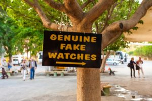 A sign pointing to 'genuine fake' goods